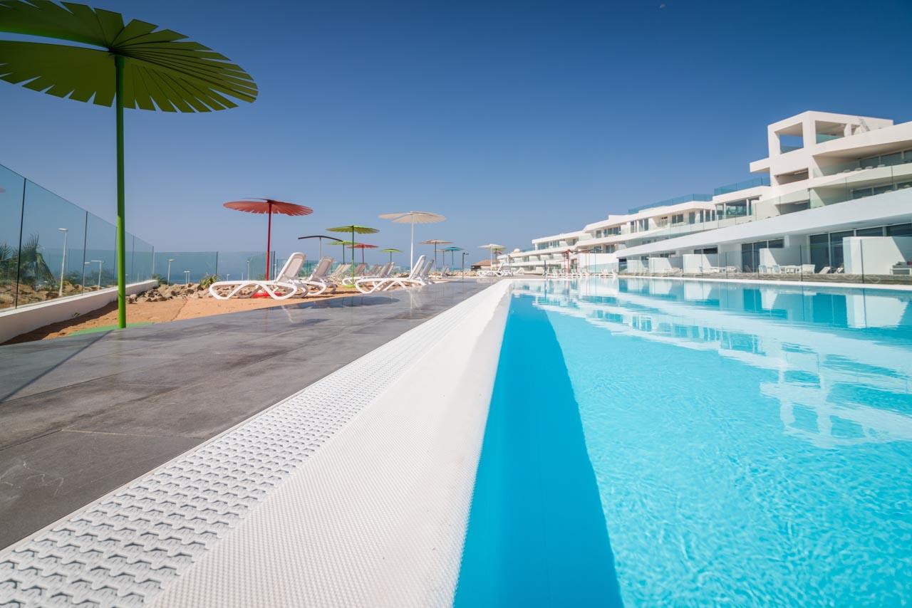 Piscina principal del hotel de lujo Baobab Suites en Tenerife Sur. Zona de arena y hamacas con vistas al mar.